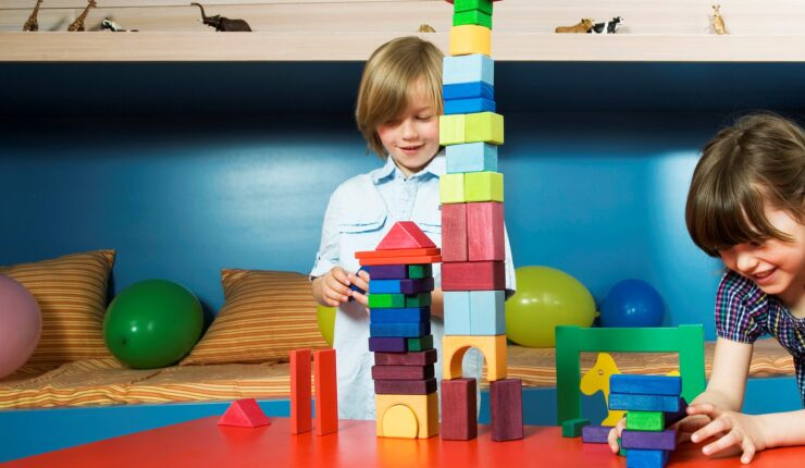 Image: Boy and gir at table playing with building blocks, smiling